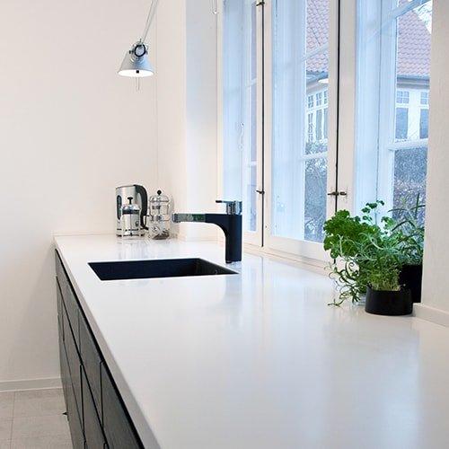 Elegant køkken med korian bordplade og grebsfrie låger